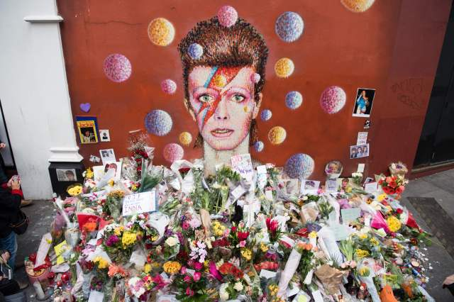 "Floral tributes are seen beneath a mural of British singer David Bowie, painted by Australian street artist James Cochran, aka Jimmy C, the day after the announcement of Bowie's death, in Brixton, south London, on January 12, 2016. Music legend David Bowie was famously private during his lifetime -- and in death, as a string of questions about the circumstances of his passing remained unanswered. His official social media accounts had announced the shock news of his death at 69 on January 11, 2016: ""David Bowie died peacefully today surrounded by his family after a courageous 18-month battle with cancer,"" adding a request for privacy for the grieving family. / AFP / LEON NEAL (Photo credit should read LEON NEAL/AFP/Getty Images)"